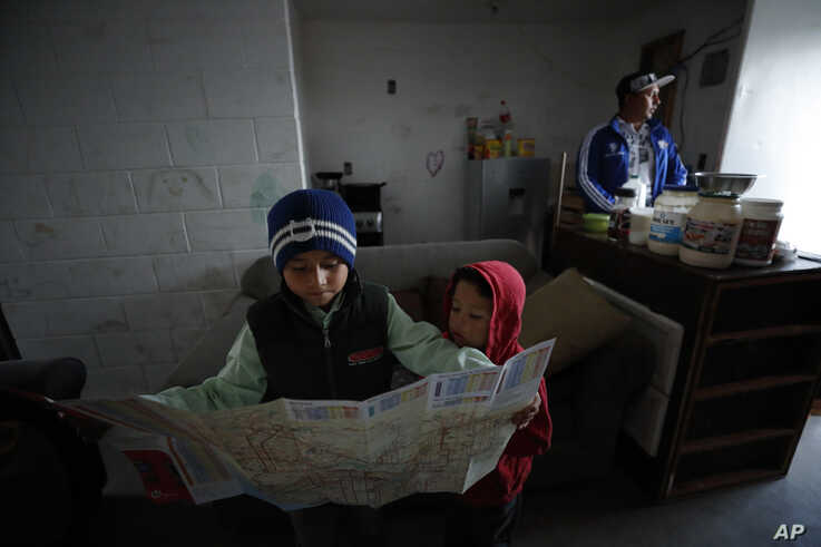 In this July 10, 2019, photo, Nahum Perla, left, studies a San Diego map with his younger brother, Carlos Isai Perla, as their…