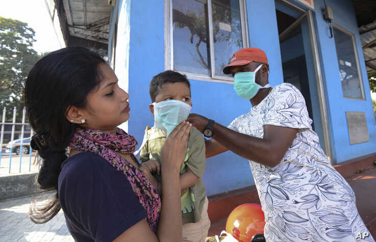 A man wearing a surgical mask makes a child wear one outside the government general hospital in Kerala State, India.