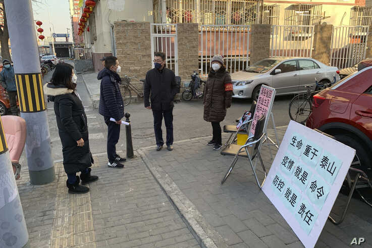 People in face masks stand near a stall to register residents who have recently returned from other provinces in a neighborhood in Beijing, Jan. 31, 2020.