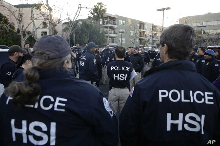 Federal agents gather at a parking lot near an upscale apartment complex, Tuesday, March 3, 2015, in Irvine, Calif. Shortly…