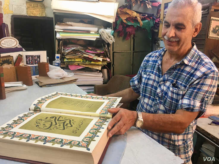 Bookbinder Mohammed Ben Sassi admires an antique quran he is working on. (VOA/Lisa Bryant)