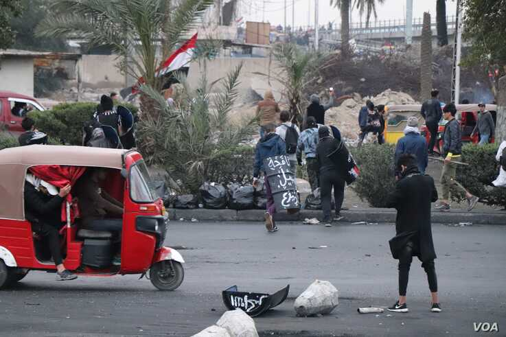 """5151: Young men charge into a struggle between protesters and riot police carrying home-made shields reading slogans like """"Attention, martyrs are advancing"""" on Jan. 24, 2020 in Baghdad. (H.Murdock/VOA)"""