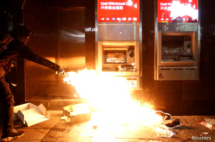 An anti-government protester feeds a flame near an ATM machine to vandalize it during an anti-government demonstration on New…