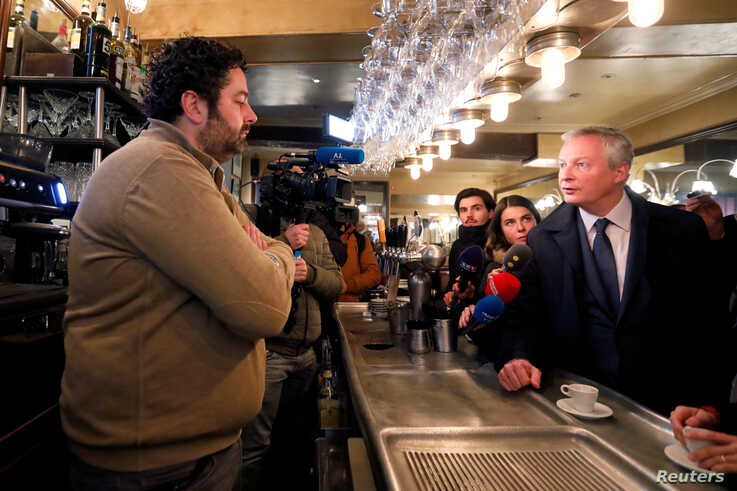 French Finance Minister Bruno Le Maire talks in a cafe as he visits shopkeepers, restaurateurs and hotel operators to assess…