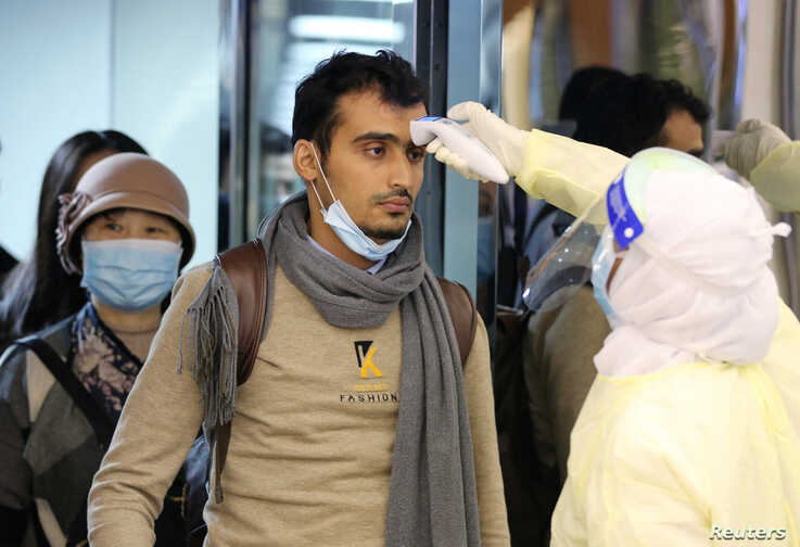Passengers coming from China wearing masks to prevent a new coronavirus are checked by Saudi Health Ministry employees upon…