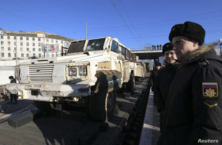 People attend a mobile exhibition installed on freight cars of a train and displaying military equipment, vehicles and weapons