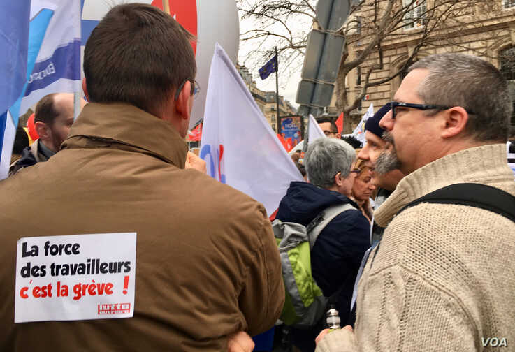 Union members at recent pension strike. Sign reads 'the force of French workers is striking.' Lisa Bryant