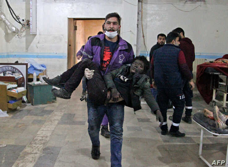 A member of the Syrian Violet Oragnization carries an injured boy at a makeshift hospital following a government airstrike on a vegetable market in Syria's last major opposition bastion of Idlib.
