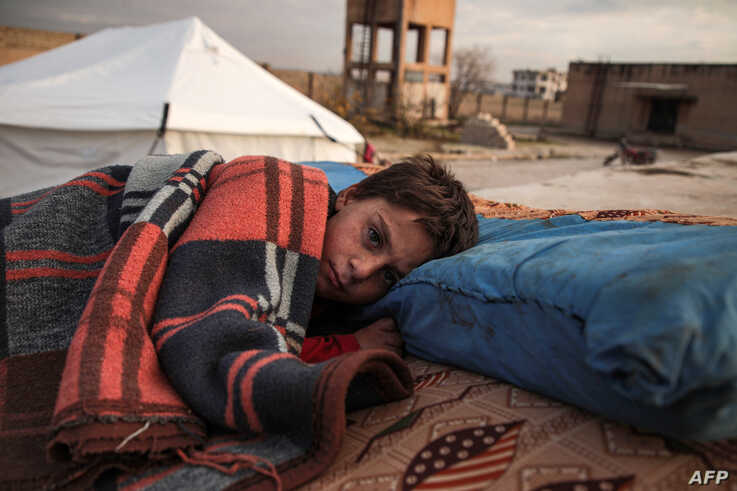 A Syrian child, one of those who fled from Idlib prvoince, sleeps in the open at a camp for the displaced near the town of Dana, Dec. 27, 2019.
