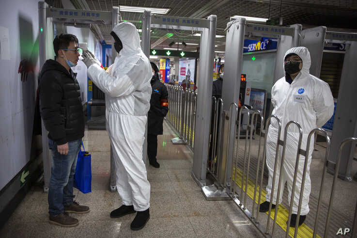 A worker wearing a protective suit takes the temperature of a passenger at the entrance to a subway station in Beijing, China, Jan. 26, 2020.
