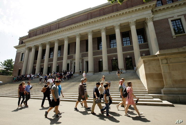 FILE - People walk past an entrance to Widener Library, behind, on the campus of Harvard University, in Cambridge, Massachusetts, July 16, 2019.