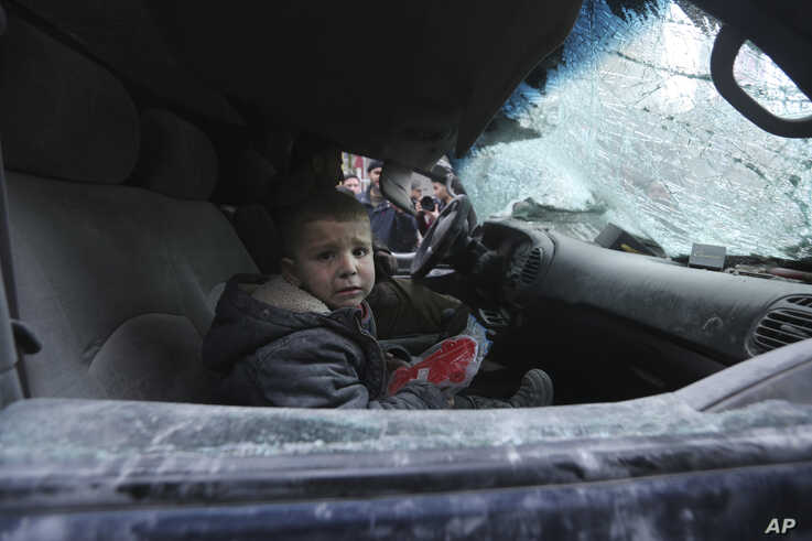 FILE - A boy, sitting in a car, cries following airstrikes by government forces, in the town of Ariha, in Idlib province, Syria, Jan. 15, 2020.