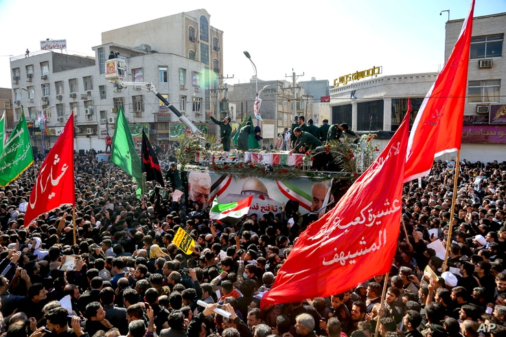 In this photo provided by The Iranian Students News Agency, ISNA, flag draped coffins of Gen. Qassem Soleimani and his comrades who were killed in Iraq in a U.S. drone strike, carried on a truck during their funeral in southwestern city of Ahvaz, Iran.