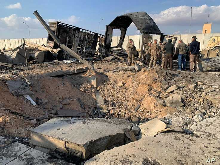 U.S. Soldiers and journalists stand near a crater caused by Iranian bombing at Ain al-Asad air base, in Anbar, Iraq, Jan. 13, 2020.