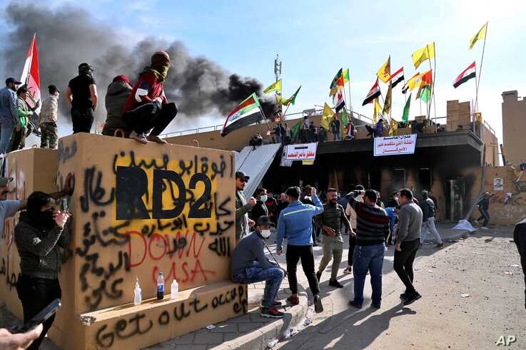 Pro-Iranian militiamen and their supporters set a fire during a sit-in in front of the U.S. embassy in Baghdad, Iraq.