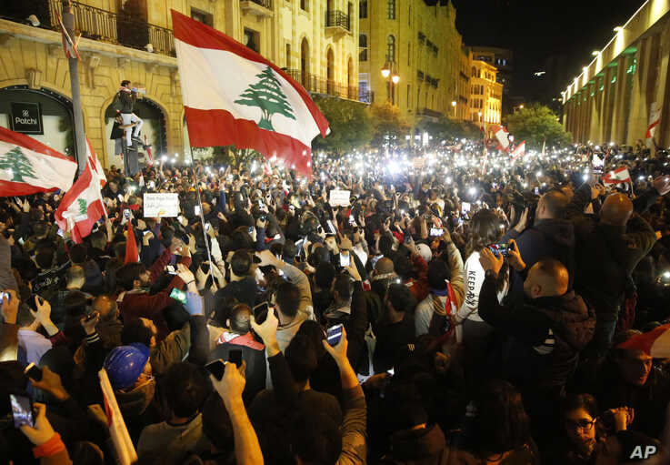 FILE - Anti-government protesters enable flashlights on their mobile phones as they shout slogans during a protest in downtown Beirut, Lebanon, Dec. 15, 2019.