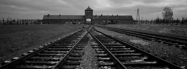 FILE - The railway tracks from where hundreds of thousands of people were directed to the gas chambers to be murdered, inside the former Nazi death camp of Auschwitz Birkenau, in Oswiecim, Poland, Dec. 7, 2019.