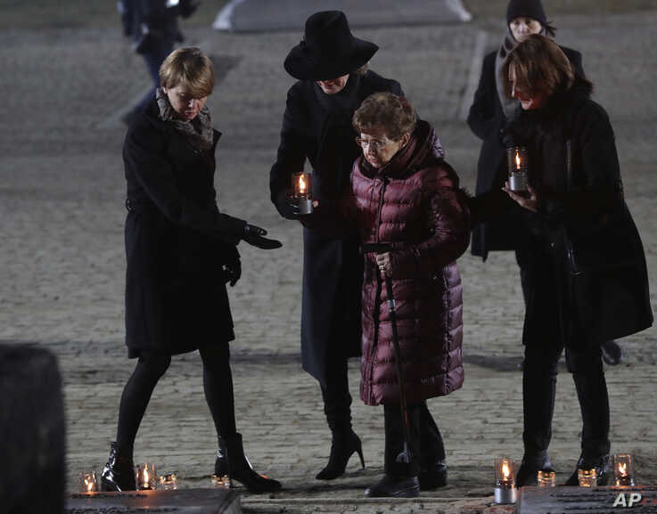 Holocaust survivor Bat-Sheva Dagan, center, is escorted as she is about to put a candle at the Auschwitz Nazi death camp in Oswiecim, Poland, Jan. 27, 2020.
