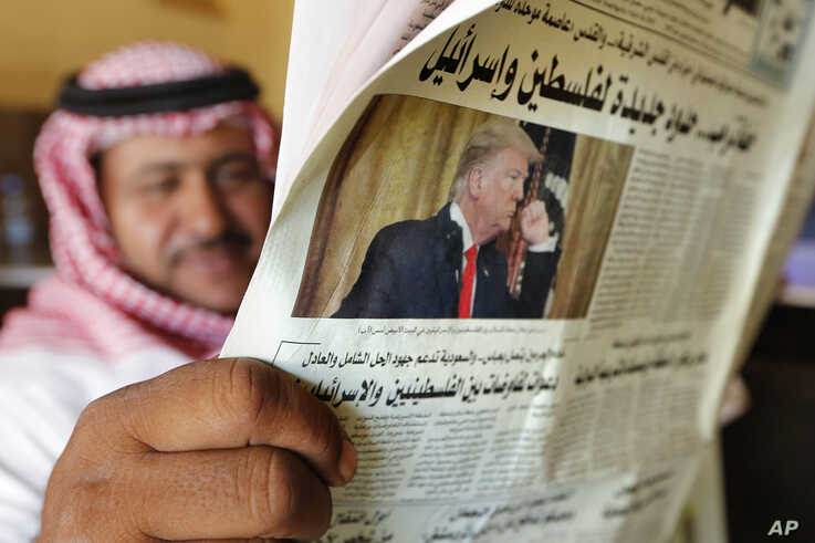 A man holds the daily Asharq Al-Awsat newspaper fronted by a picture of U.S.President Donald Trump, at a coffee shop in Jiddah, Saudi Arabia, Jan. 29, 2020, following Trump's unveiling of a Mideast peace plan.