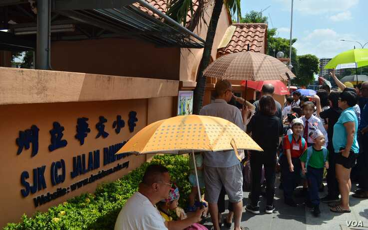 Parents pick up their children outside a Chinese-language primary school in Kuala Lumpur. (Photo: Zsombor Peter/VOA)