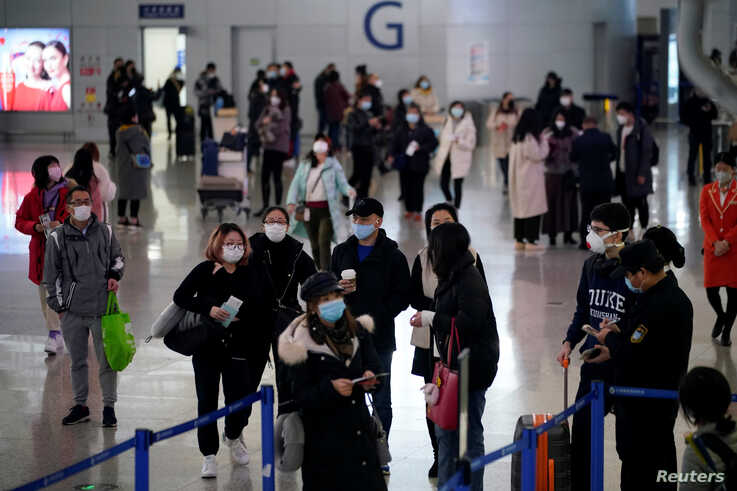 Passengers wearing masks are seen at Pudong International Airport, in Shanghai, China, Jan. 27, 2020.