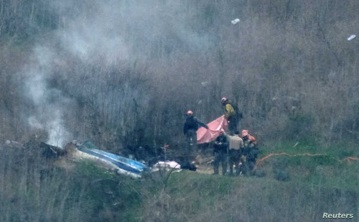 Law enforcement officers investigate the scene of a helicopter crash that killed retired basketball star Kobe Bryant and others, in Calabasas, near Los Angeles, California, Jan. 26, 2020.