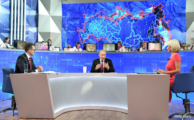 FILE - Russian President Vladimir Putin (C) speaks during an annual televised call-in show in Moscow, Russia, June 20, 2019.