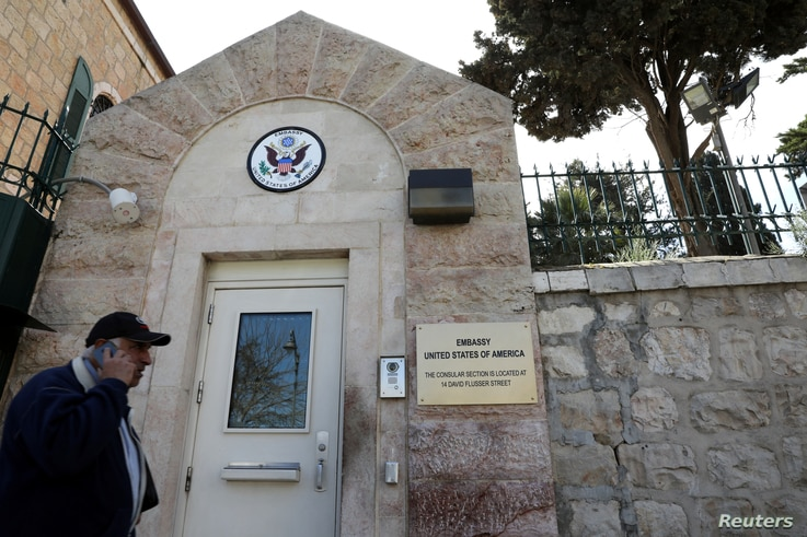 """FILE - A man walks past a wall with plaques bearing the words """"Embassy United States of America"""" at the premises of the former U.S. Consulate in Jerusalem, March 12, 2019."""