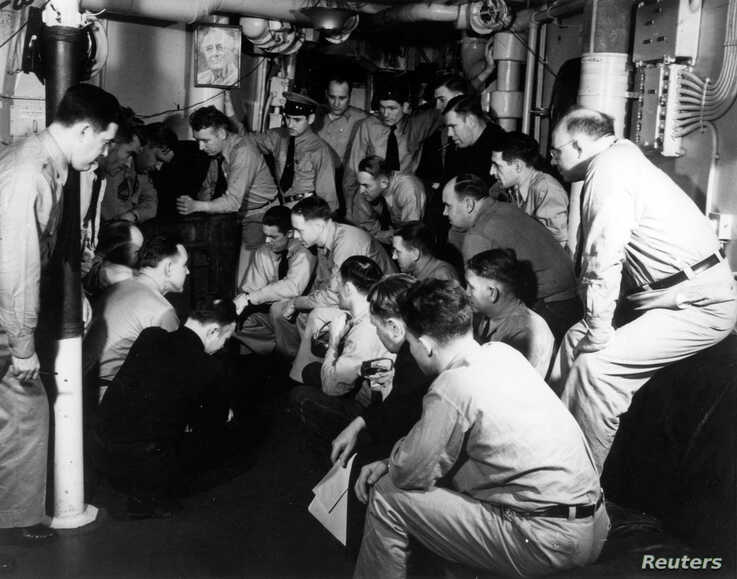 FILE - Naval officers listen to a radio broadcast of President Franklin D. Roosevelt's address to the Congress requesting a declaration of War against the Axis powers, Dec. 8, 1941.