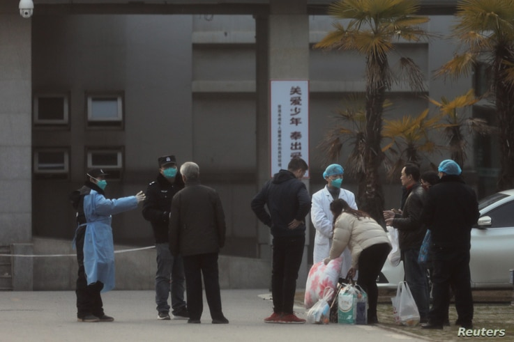 Medical staff and security personnel stop patients' family members from being too close to the Jinyintan hospital, where the patients with pneumonia caused by the new strain of coronavirus are being treated, in Wuhan, Hubei province, China, Jan. 20, 2020.