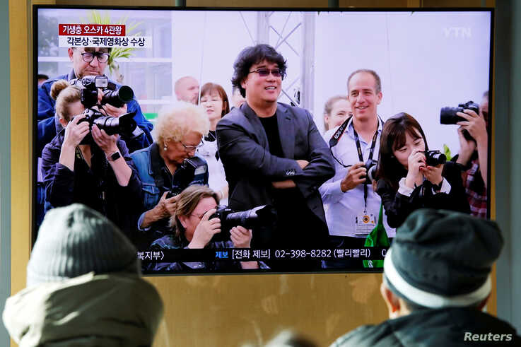 FILE - People watch a TV broadcasting a news report on South Korean director Bong Joon-ho who won four Oscars