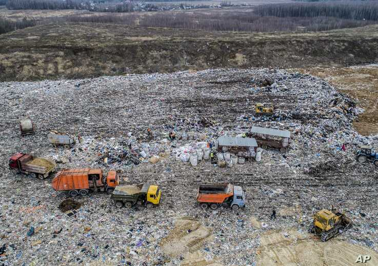 In this photo taken on  April 20, 2018, garbage trucks unload the trash at the Volovichi landfill near Kolomna, Russia.