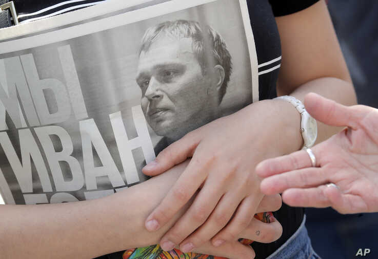 A supporter of Ivan Golunov, an investigative journalist who worked for the independent website Meduza, holds a newspaper