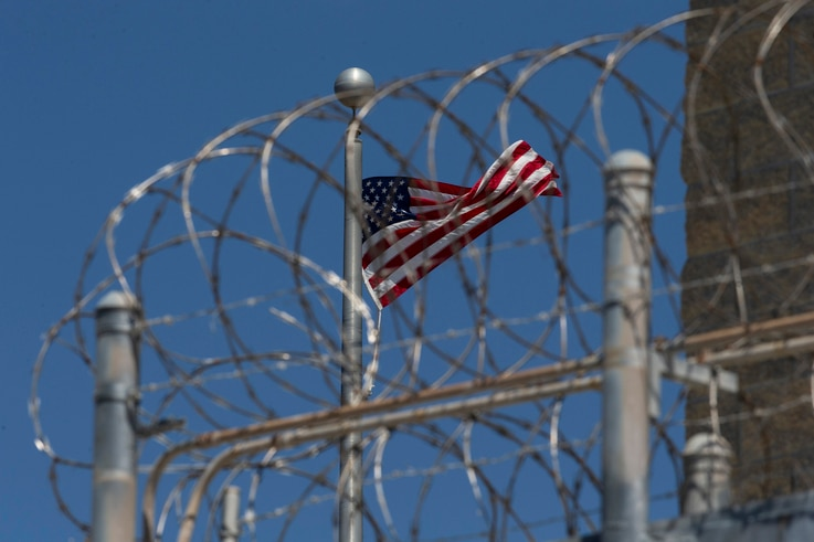 FILE - In this April 17, 2019 file photo reviewed by U.S. military officials, a U.S. flag flies inside the razor wire of the Camp VI detention facility in Guantanamo Bay Naval Base, Cuba.