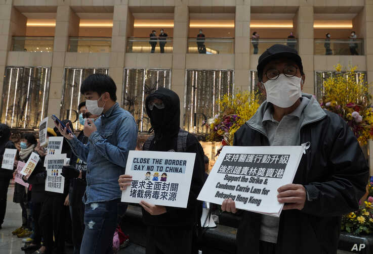 """Protesters wearing masks hold placards reads"""" Close the border, say no to China"""" during a protest at a mall in Hong Kong,…"""