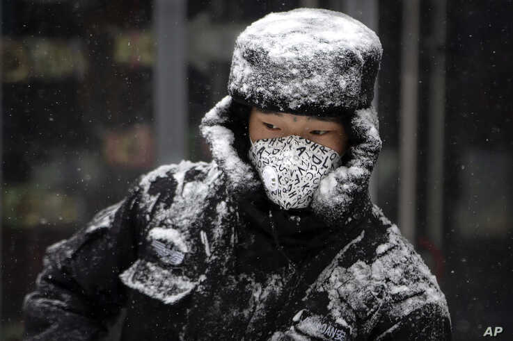 A security guard wears a face mask as he sweeps snow along a pedestrian shopping street during a snowfall in Beijing, Feb. 5, 2020.