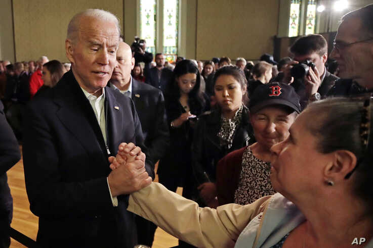 Democratic presidential candidate former Vice President Joe Biden holds a woman's hand while speaking a campaign event.