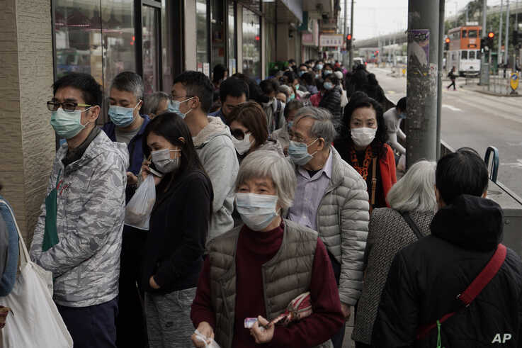 People queue up to buy face masks in Hong Kong, Friday, Feb. 7, 2020. Japan on Friday reported 41 new cases of a virus on a…