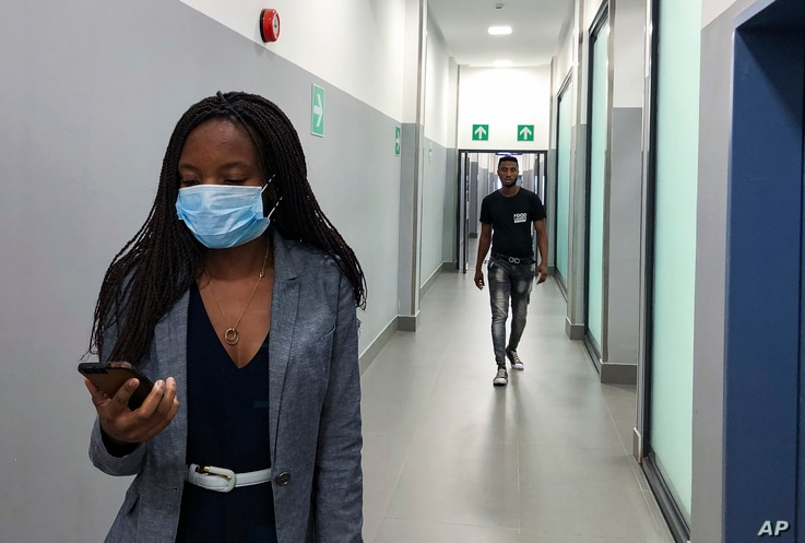 In Feb. 6, 2020, photo, a masked woman walks in a corridor of a shopping mall in Kitwe, Zambia. The coronavirus that has spread…