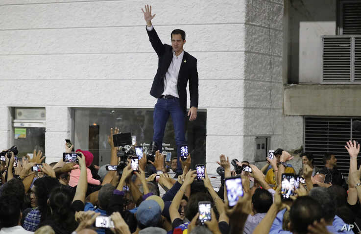Opposition leader Juan Guaido waves to supporters during a rally at Bolivar Plaza in Chacao, Venezuela, Feb. 11, 2020. Guaido returned home from a tour of nations that back his effort to oust socialist leader Nicolas Maduro.