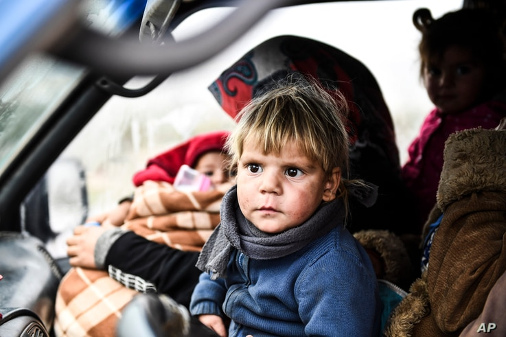 Syrian civilians flee from Idlib in rain toward the north to find safety inside Syria near the border with Turkey, Thursday,…