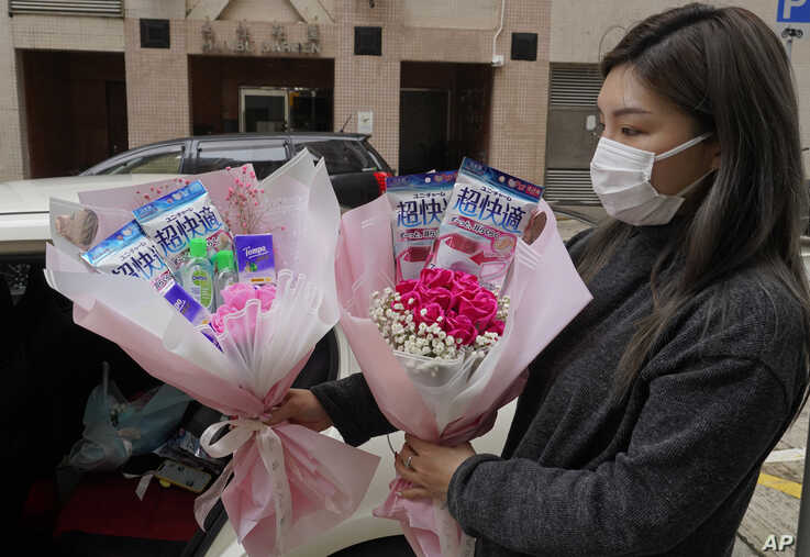 Flower shop owner Iris Leung wears her protective face mask as she delivers flowers with masks to customers on Valentine's Day in Hong Kong, Feb. 14, 2020.