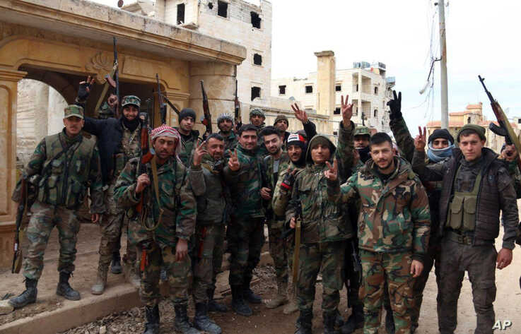 In this photo released Sunday, Feb. 16, 2020 by the Syrian official news agency SANA, Syrian army soldiers flash the victory sign in the Rashideen neighborhood, in Aleppo province, Syria.