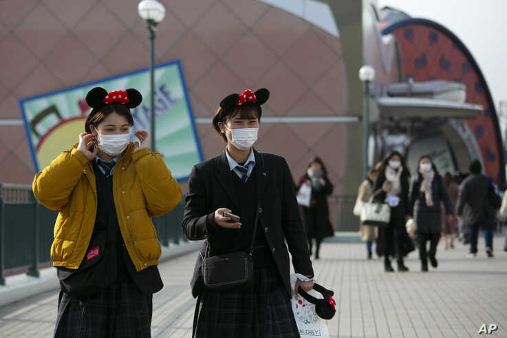 Two visitors with masks and Minnie Mouse ear headbands leave Tokyo Disneyland in Urayasu, near Tokyo, Feb. 28, 2020.