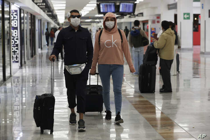 A couple wears protective masks as a precaution against the spread of the new coronavirus at the airport in Mexico City.