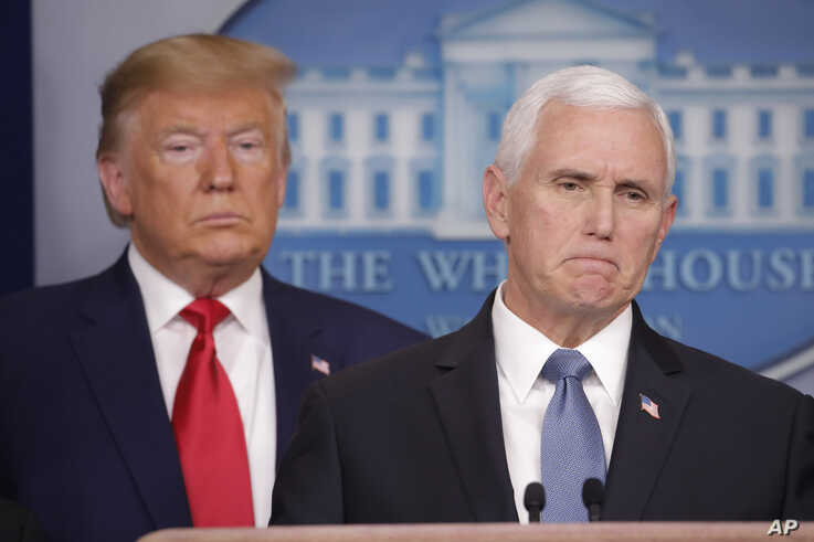 President Donald Trump, left, listens to Vice President Mike Pence, right, as he pauses while speaking to members of the media.