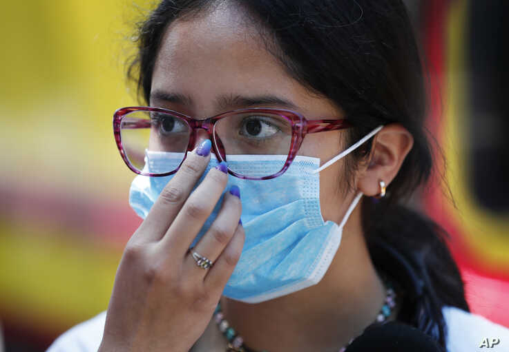 A teen wears a medical mask as a precaution against the spread of the new coronavirus, during an outing in Mexico City