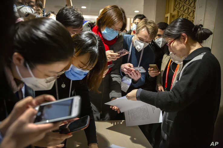 Journalists wearing face masks look at a government statement prior to a press conference about the coronavirus outbreak, in Beijing, China, Jan. 26, 2020. Meanwhile, citizen journalists are challenging the official narrative with their own reporting.