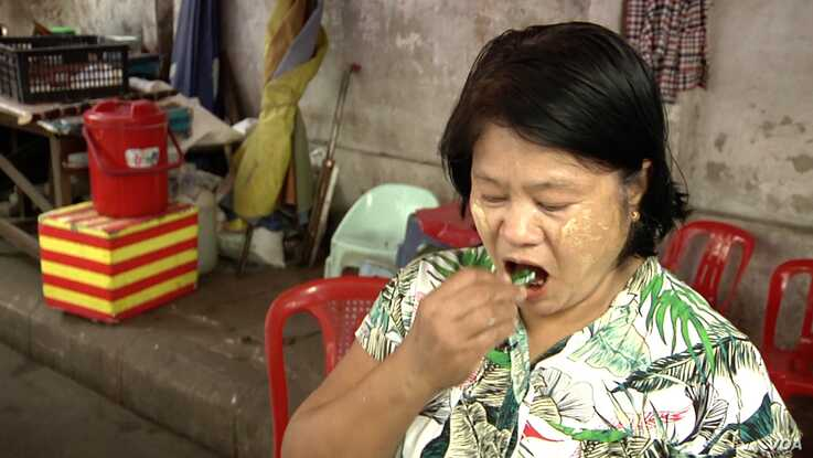 """Ni Ni Wah puts a betel quid in her mouth. She dismisses the risks of cancer saying """"mouth cancer happens to people who keep betel quids in their mouth all night while they sleep."""" (Dave Grunebaum/VOA)"""