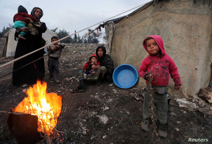 Displaced Syrian women and children, who fled from southern Idlib, gather around a fire in Afrin, Syria February 6, 2020…